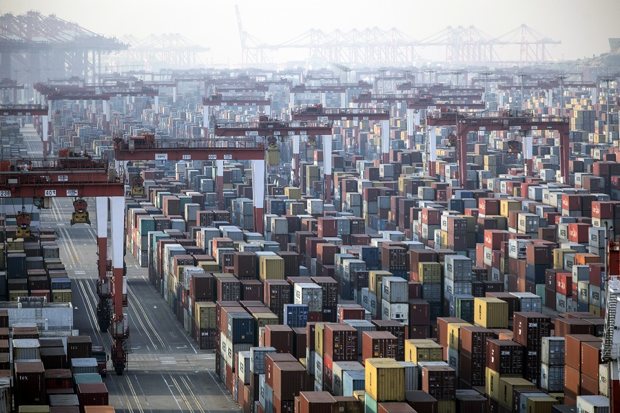 Shipping containers next to gantry cranes at the Yangshan Deep Water Port in Shanghai, China, 11 January 2021. (Qilai Shen/Bloomberg)