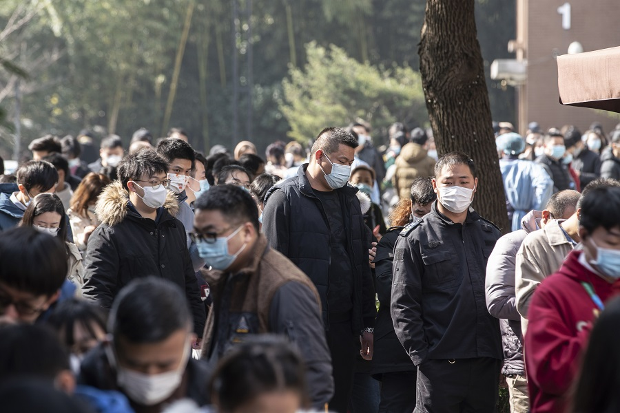 People wearing protective masks stand in line at a Covid-19 testing center in Shanghai, China, on 6 February 2021. (Qilai Shen/Bloomberg)