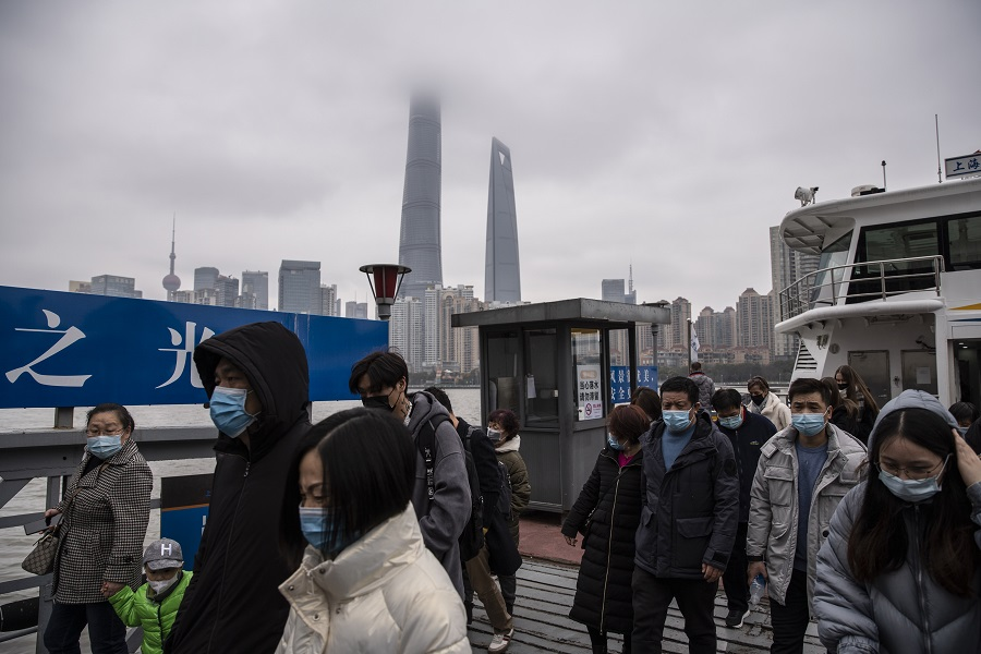 People wearing protective masks disembark from a ferry after crossing the Huangpu River in Shanghai, China, on 12 February 2021. (Qilai Shen/Bloomberg)