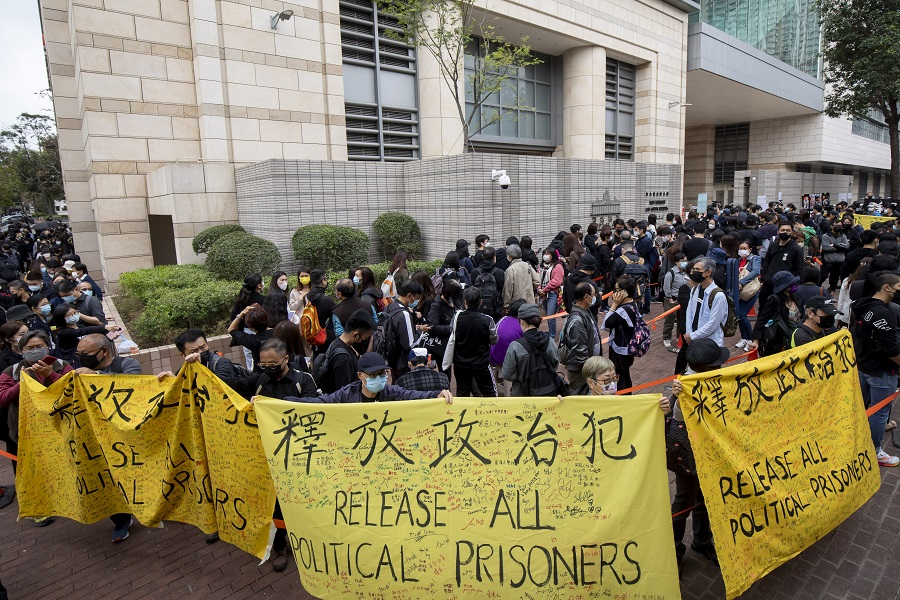 "Pro-democracy demonstrators hold banners reading ""Release all political prisoners"" while waiting to enter the West Kowloon Magistrates' Courts ahead of a hearing for 47 opposition activists charged with violating the city's national security law in Hong Kong, China, on 1 March 2021. (Paul Yeung/Bloomberg)"