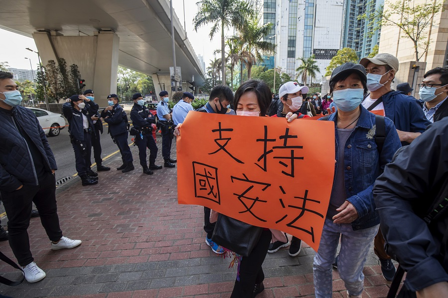 "A pro-government demonstrator holds a placard reading ""Support national security law"" outside the West Kowloon Magistrates' Courts ahead of a hearing for 47 opposition activists charged with violating the city's national security legislation in Hong Kong, China, on 1 March 2021. (Paul Yeung/Bloomberg)"