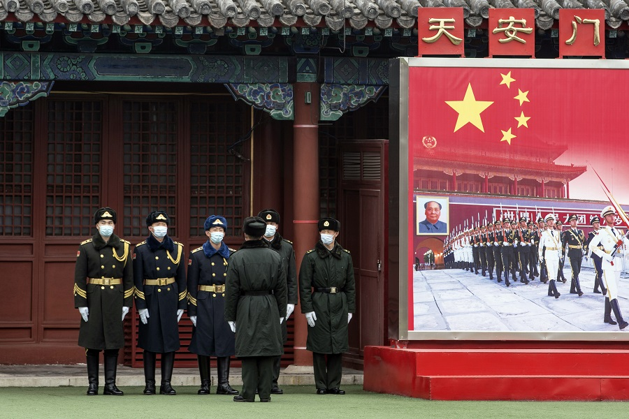 Members of the People's Liberation Army (PLA) honour guard stand next to a banner near the Forbidden City in Beijing, China, on 3 March 2021. (Qilai Shen/Bloomberg)