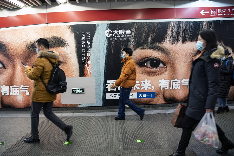 People wearing protective masks walk past an advertisement at a subway station in Beijing, China, on 3 March 2021. (Qilai Shen/Bloomberg)