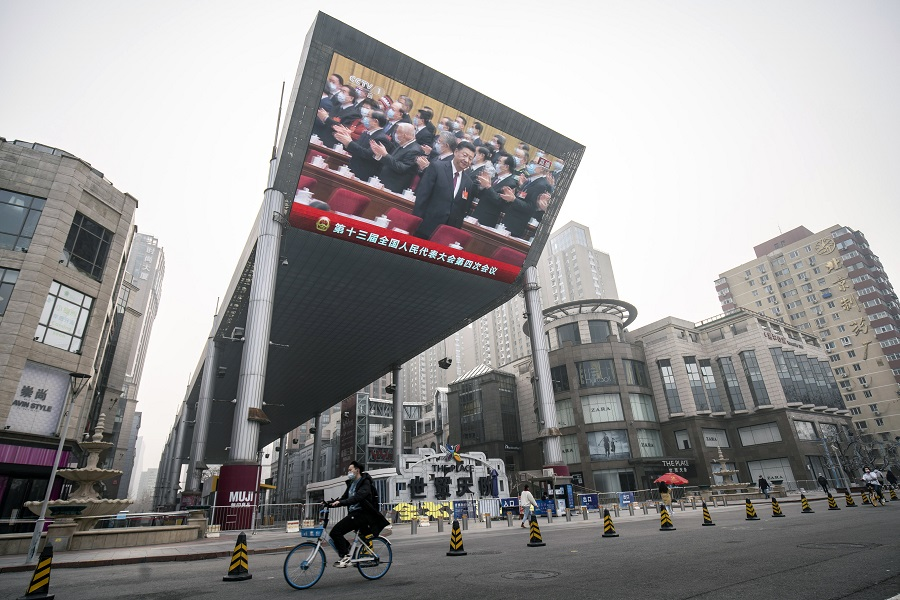 A cyclist rides past a screen showing a live news broadcast of Chinese President Xi Jinping arriving at the National People's Congress in Beijing, China, on 5 March 2021. (Qilai Shen/Bloomberg)