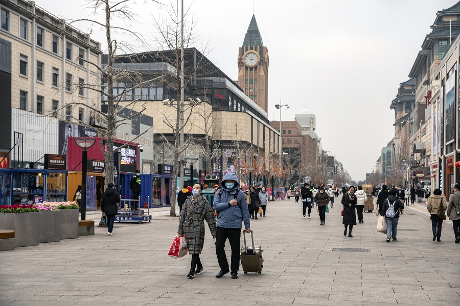 Pedestrians wearing protective masks walk past stores in the Wangfujing shopping area of Beijing, China, on 5 March 2021. (Qilai Shen/Bloomberg)