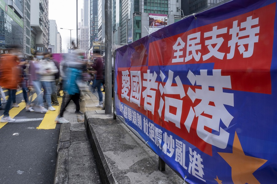 """Pedestrians walk past a banner reading """"The People Support Patriots Ruling Hong Kong"""" in the middle of a road in Hong Kong, China, on 6 March 2021. (Justin Chin/Bloomberg)"""