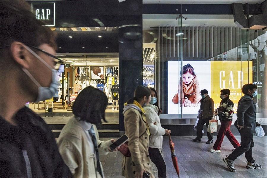 Pedestrians wearing protective masks walk past a Gap Inc. store in Shanghai, China, 9 March 2021. (Qilai Shen/Bloomberg)