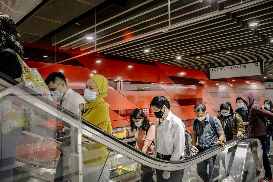Commuters ride an escalator in Kuala Lumpur, Malaysia, on 5 April 2021. (Ian Teh/Bloomberg)