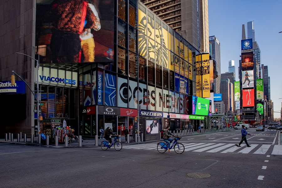 Cyclists cross a street in the Times Square neighborhood of New York, US, on 8 April 2021. (Amir Hamja/Bloomberg)