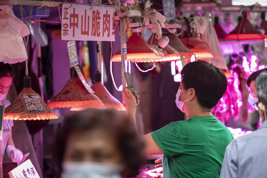 A customer uses a mobile phone to scan a QR code to make a digital payment at an open-air market in Guangzhou, China, on 24 May 2021. (Qilai Shen/Bloomberg)