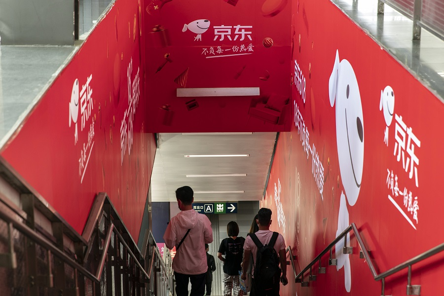 Pedestrians walk past a JD.com Inc. advertisement at a subway station in Beijing, China, on 26 May 2021. (Qilai Shen/Bloomberg)