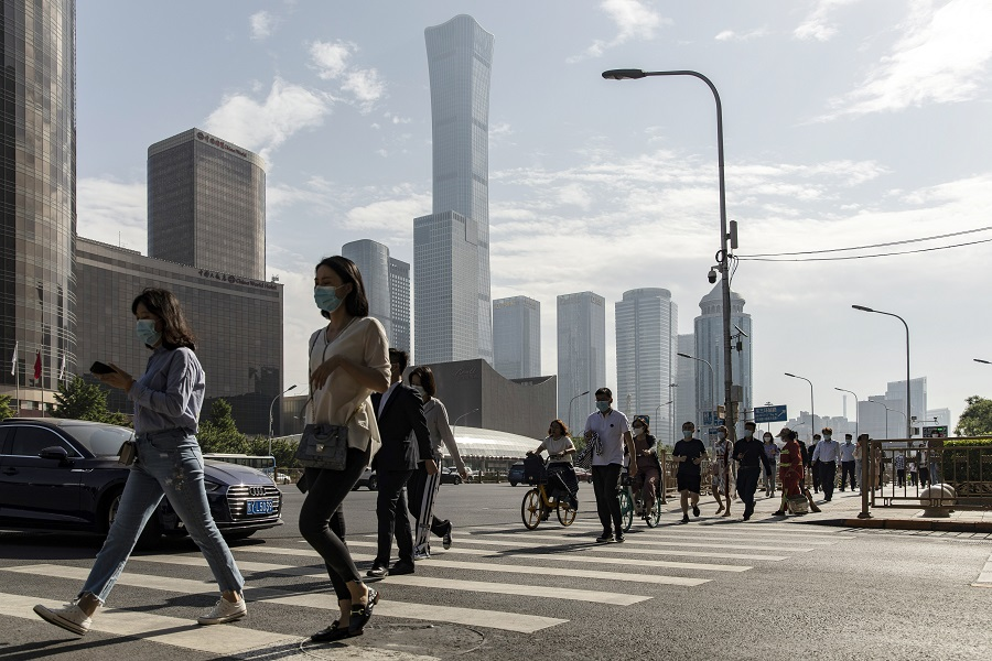 Pedestrians wearing protective masks walk across a road in the central business district in Beijing, China, on 27 May 2021. (Qilai Shen/Bloomberg)