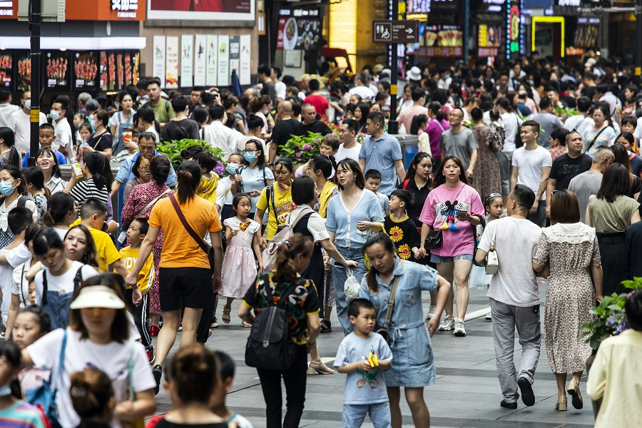 People walk along a road in a shopping area in Chongqing, China, on 1 June 2021. (Qilai Shen/Bloomberg)
