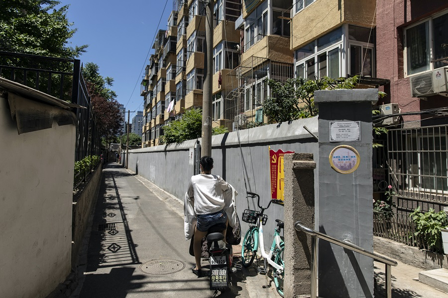A motorist sits on a motorcycle in front of apartment buildings in a residential area in Beijing, China, on 28 May 2021. (Qilai Shen/Bloomberg)