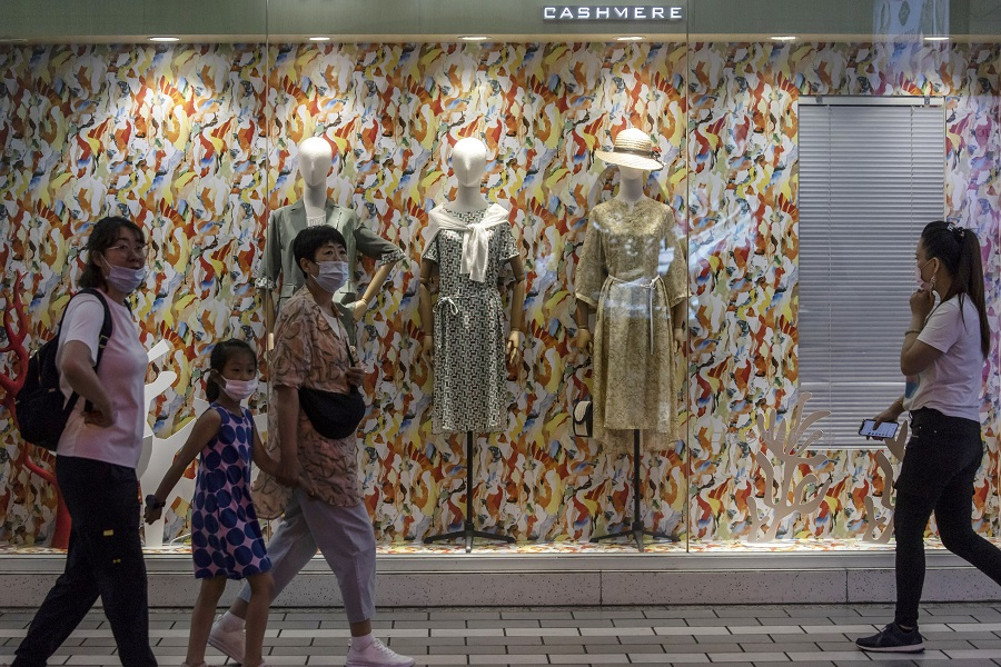 Shoppers and pedestrians walk past a store at Nanjing Road in Shanghai, China, on 6 June 2021. (Qilai Shen/Bloomberg)