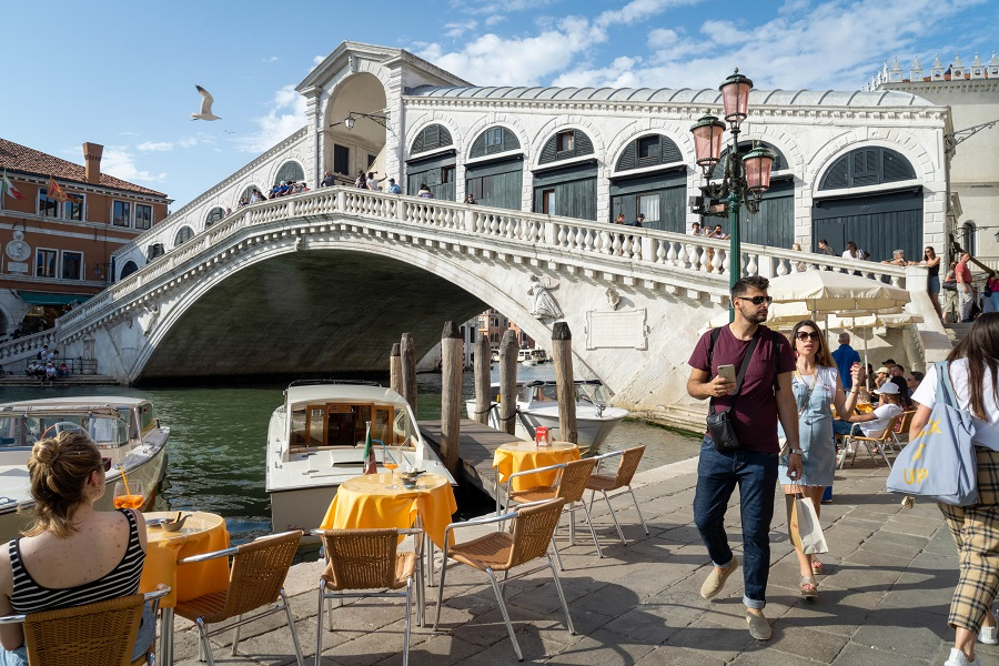 Tourists pass a cafe terrace at the Rialto Bridge in Venice, Italy, on 5 June 2021. (Giulia Marchi/Bloomberg)