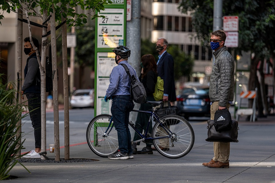 Commuters wearing protective masks wait for a bus in San Francisco, California, US, on 9 June 2021. (David Paul Morris/Bloomberg)