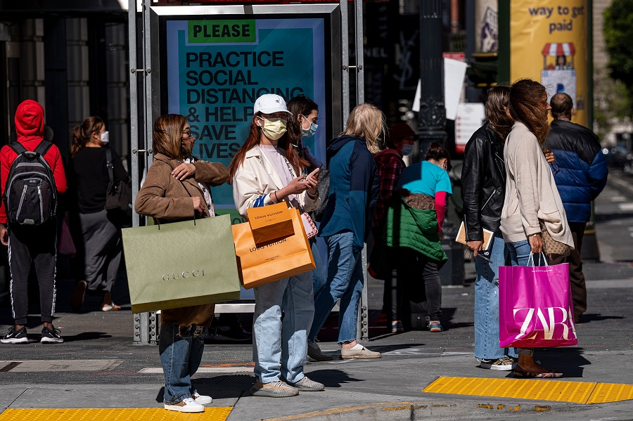 People wearing protective masks carry shopping bags while waiting to cross Geary Street in San Francisco, California, US, on 10 June 2021. (David Paul Morris/Bloomberg)