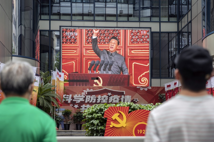 edestrians watch a screen showing a live news broadcast of Chinese President Xi Jinping speaking at a ceremony marking the centenary of the Chinese Community Party, taking place at Beijing's Tiananmen Square, in Shanghai, China, on 1 July 2021. (Qilai Shen/Bloomberg)