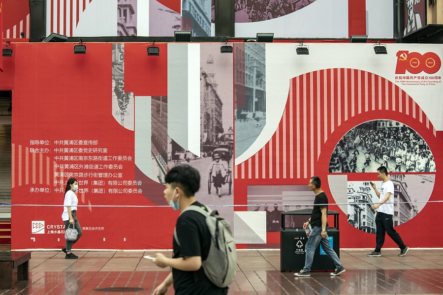 Pedestrians walk past a display celebrating the centenary of the Chinese Community Party in Shanghai, China, on 1 July 2021. (Qilai Shen/Bloomberg)