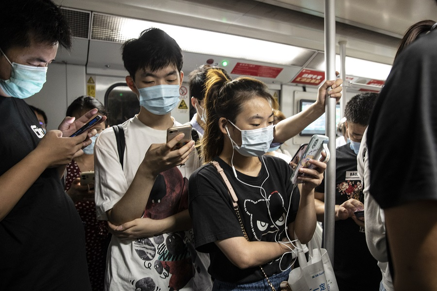 Commuters wearing protective masks ride on board a subway train during the morning rush hour in Shanghai, China, on 6 August 2021. (Qilai Shen/Bloomberg)