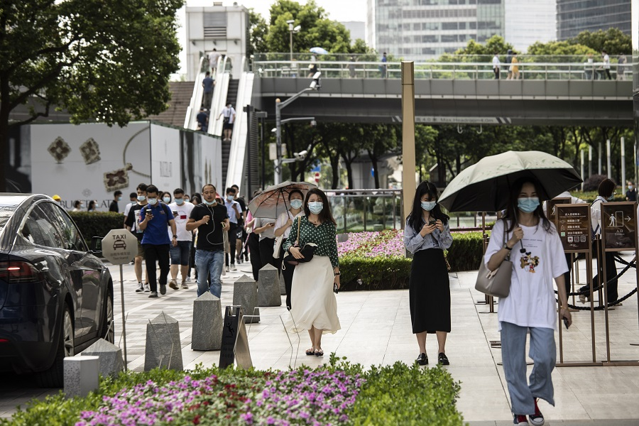 Pedestrians wearing protective masks make their way through the financial district during the morning rush hour in Shanghai, China, 6 August 2021. (Qilai Shen/Bloomberg)