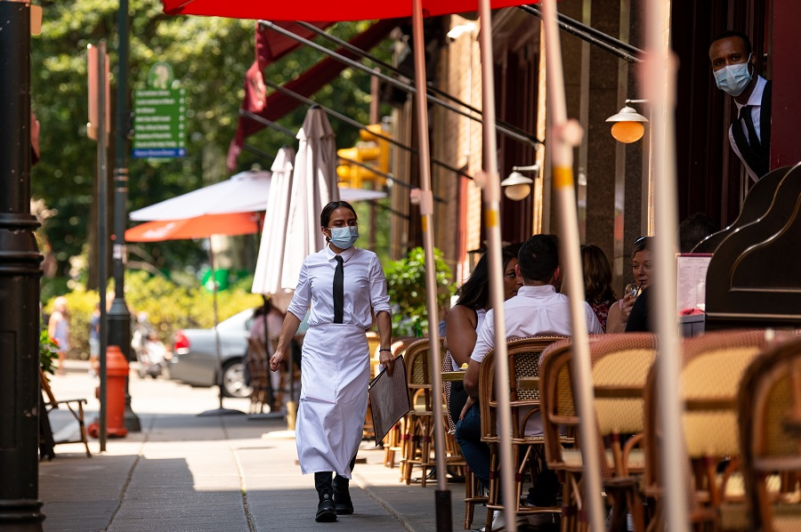 A server wearing a protective mask carries menus in the outdoor dining section of a restaurant in Philadelphia, Pennsylvania, US, on 12 August 2021. (Kriston Jae Bethel/Bloomberg)