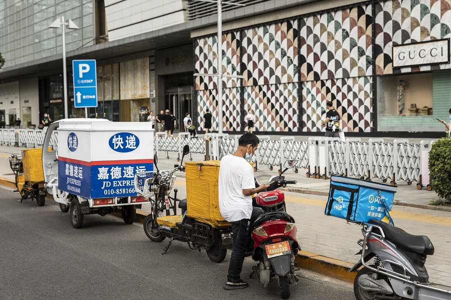 A delivery driver stands with this motorcycle near an upscale shopping mall in Beijing, China, on 25 August 2021. (Qilai Shen/Bloomberg)