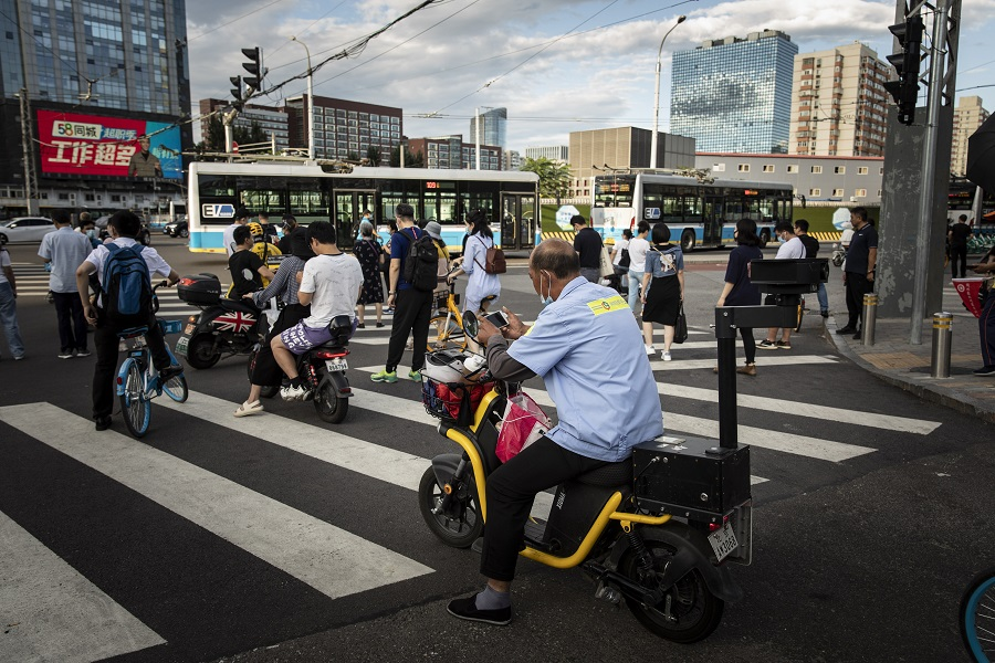 Commuters wait at a traffic intersection in Beijing, China, on 25 August 2021. (Qilai Shen/Bloomberg)