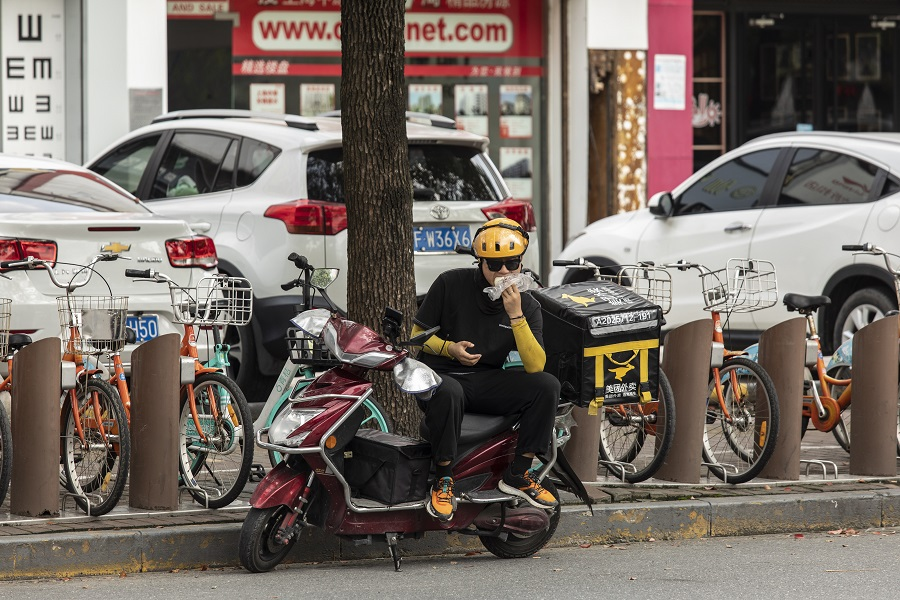 A delivery driver for Meituan takes a quick bite while sitting on his scooter in Shanghai, China, on 30 August 2021. (Qilai Shen/Bloomberg)