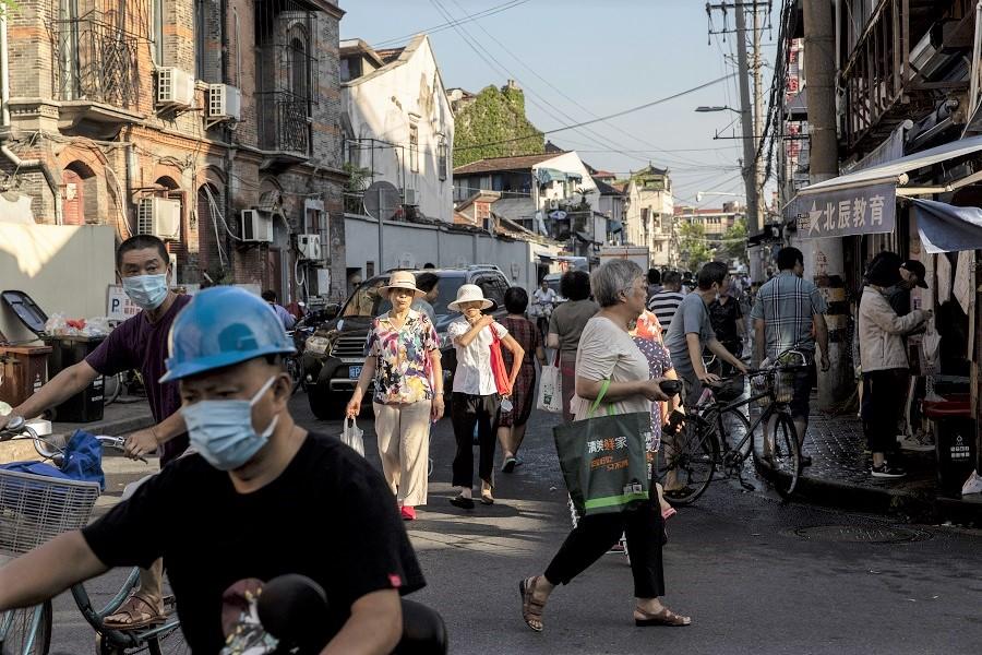 Residents walk past street stalls in an older neighborhood in Shanghai, China, on 30 August 2021. (Qilai Shen/Bloomberg)
