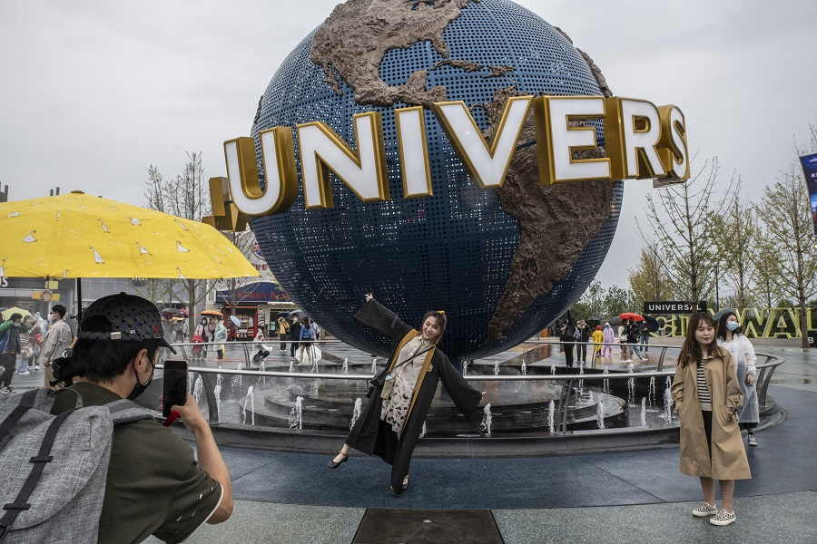 Visitors pose for photos at the entrance of the Universal Studios Beijing theme park in Beijing, China, on 20 September 2021. (Gilles Sabrie/Bloomberg)