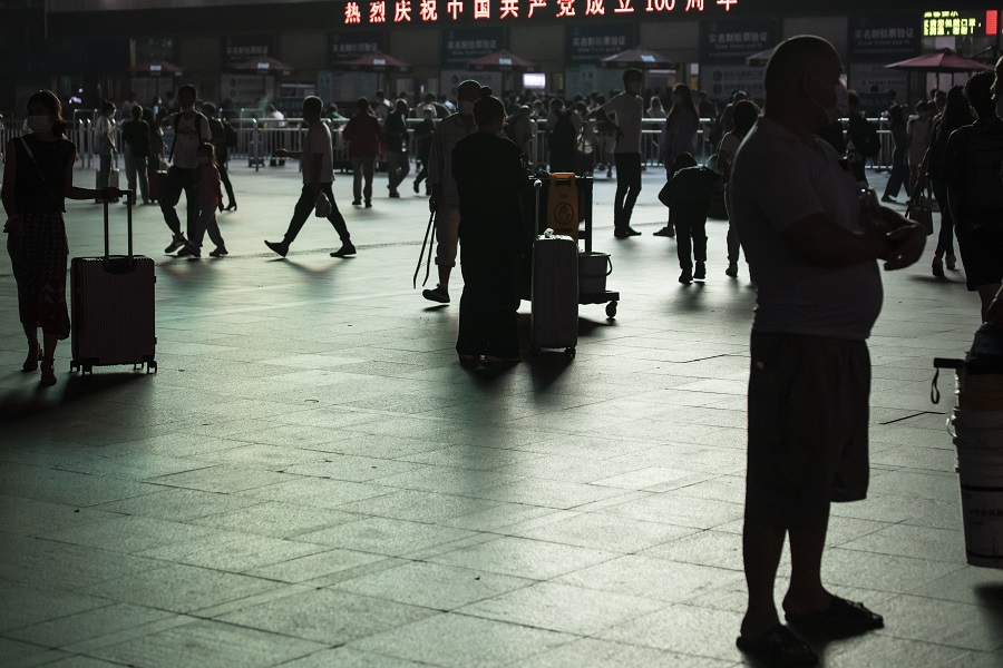 Travelers gather in the square outside Shanghai Railway Station in Shanghai, China, on 29 September 2021. (Qilai Shen/Bloomberg)