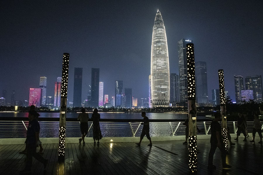 Pedestrians pass in front of the KK100 skyscraper while walking through a park at night in Shenzhen, China, on 30 September 2021. (Gilles Sabrie/Bloomberg)