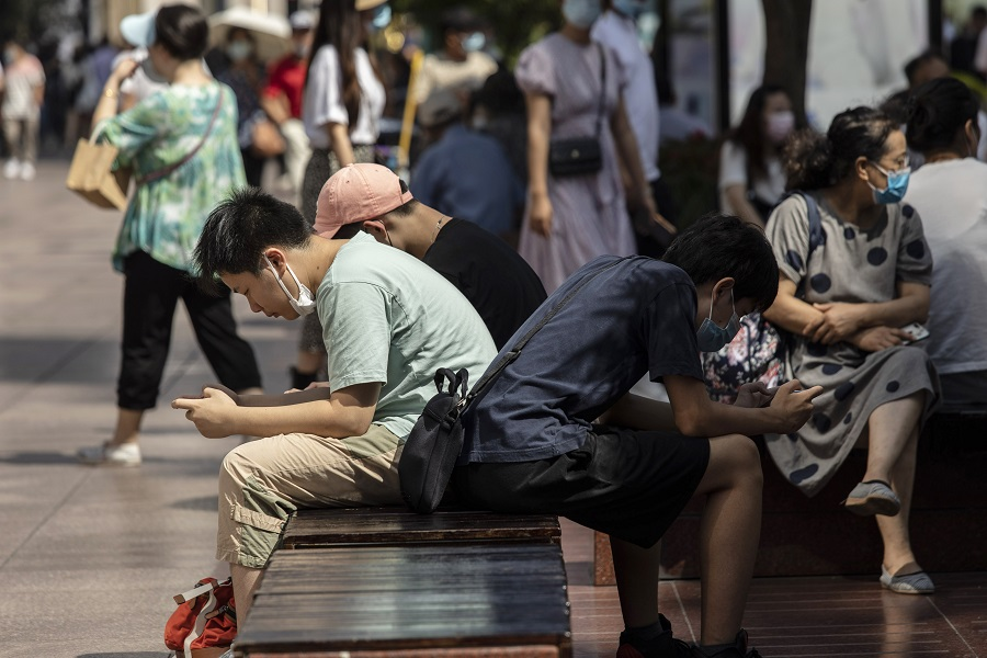 Teenagers play games on their phone while sitting on a bench at Nanjing Road East in Shanghai, China, on 3 October 2021. (Qilai Shen/Bloomberg)