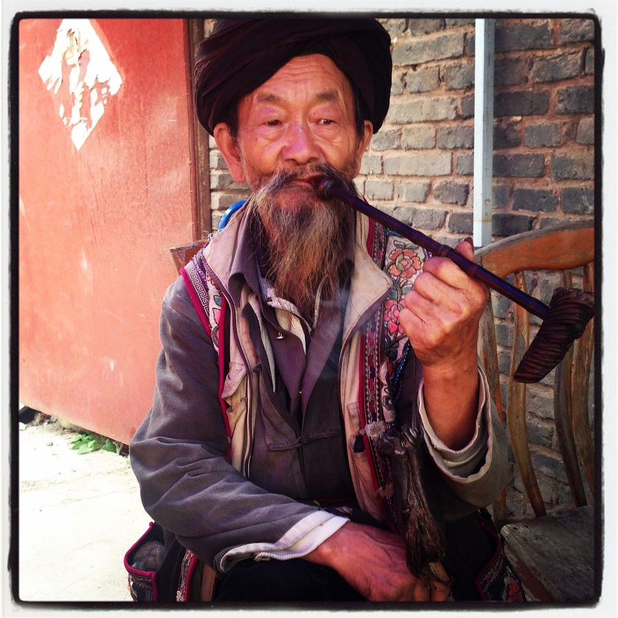 Taking a break. A local at the market in Shigu (石鼓古镇) smoking a pipe.