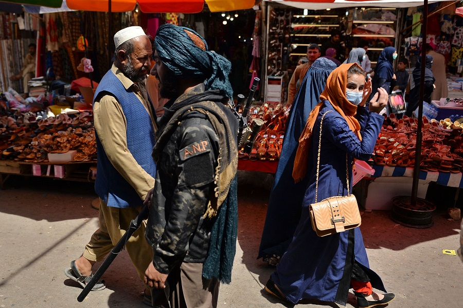 A Taliban fighter (centre) walks past shoppers along Mandawi market in Kabul on 1 September 2021. (Hoshang Hashimi/AFP)