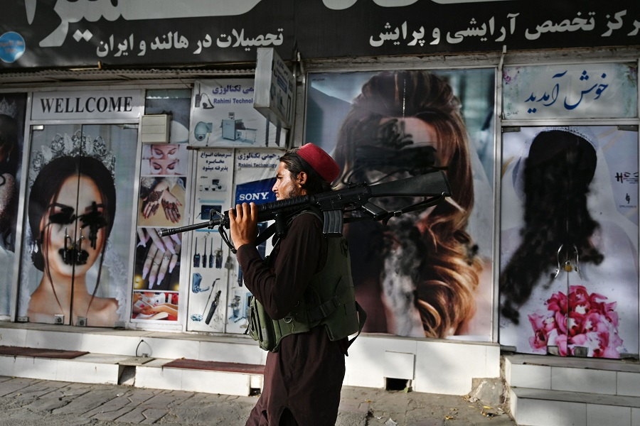 A Taliban fighter walks past a beauty salon with images of women defaced using spray paint in Shahr-e Naw in Kabul, Afghanistan, on 18 August 2021. (Wakil Kohsar/AFP)