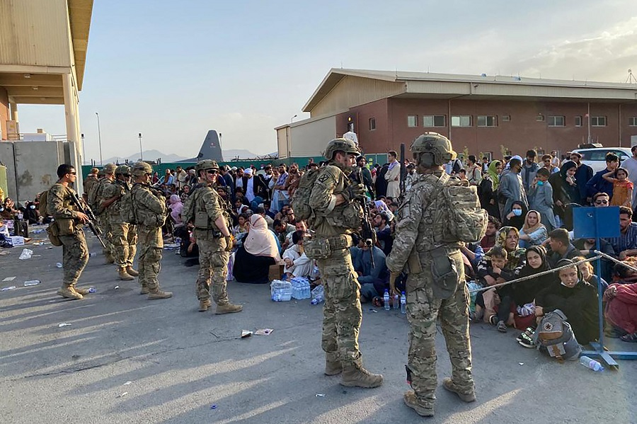 US soldiers stand guard as Afghan people wait to board a US military aircraft to leave Afghanistan, at the military airport in Kabul, Afghanistan, on 19 August 2021. (Shakib Rahmani/AFP)
