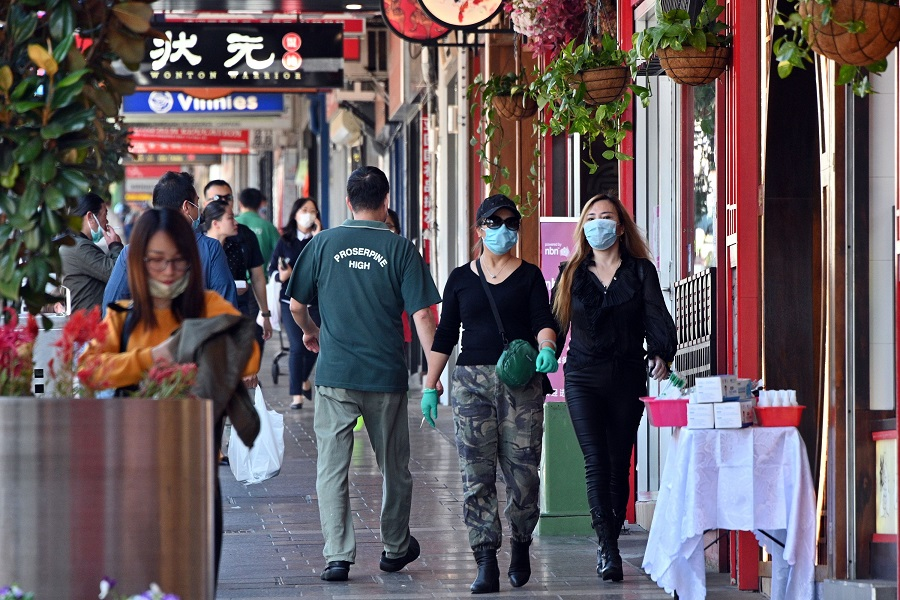 People wearing face masks walk in the Burwood suburb of Sydney on 14 April 2020, amid the Covid-19 pandemic. (Saeed Khan/AFP)