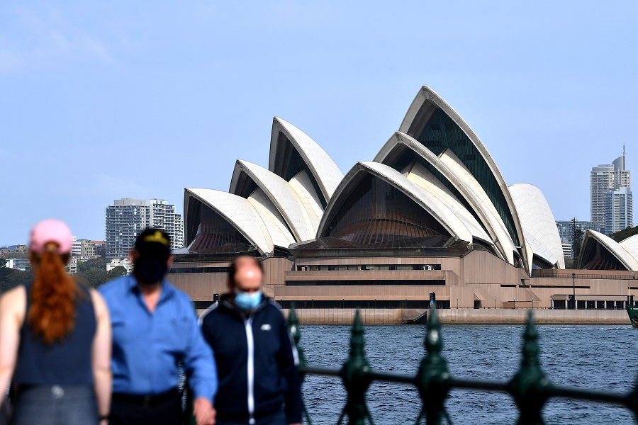 People wearing face masks walk in front of the Sydney Opera House, in Sydney, Australia, on 10 September 2021. (Saeed Khan/AFP)