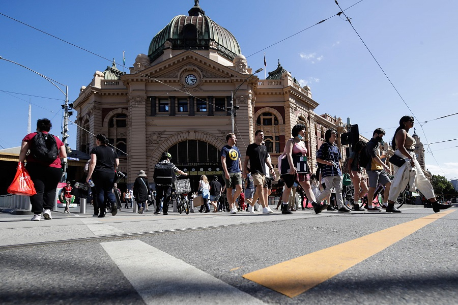 People cross a street in Melbourne on 12 February 2021. (Con Chronis/AFP)