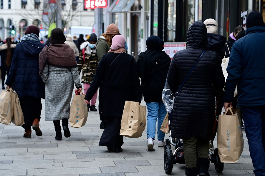 People carrying several shopping bags walk on a street in Brussels, Belgium, on 4 January 2021 (Laurie Dieffembacq/Belga/AFP)