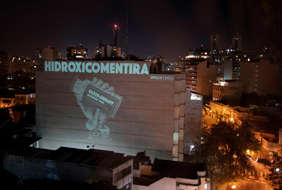 """A projection on a building plays with the words """"hydroxychloroquine"""" and """"lie"""" as a protest against Brazilian President Jair Bolsonaro, a fervent advocate of the drug, during a tribute honouring the 100,000 victims who died of the Covid-19 coronavirus in Brazil, in Botafogo neighbourhood in Rio de Janeiro, Brazil, on 8 August 2020. (Mauro Pimentel/AFP)"""
