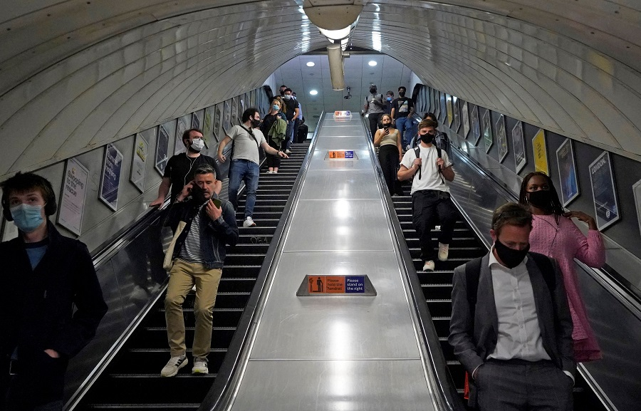 Commuters travel on an escalator in a Transport for London (TFL) underground train station in central London on 7 June 2021. (Niklas Halle'n/AFP)