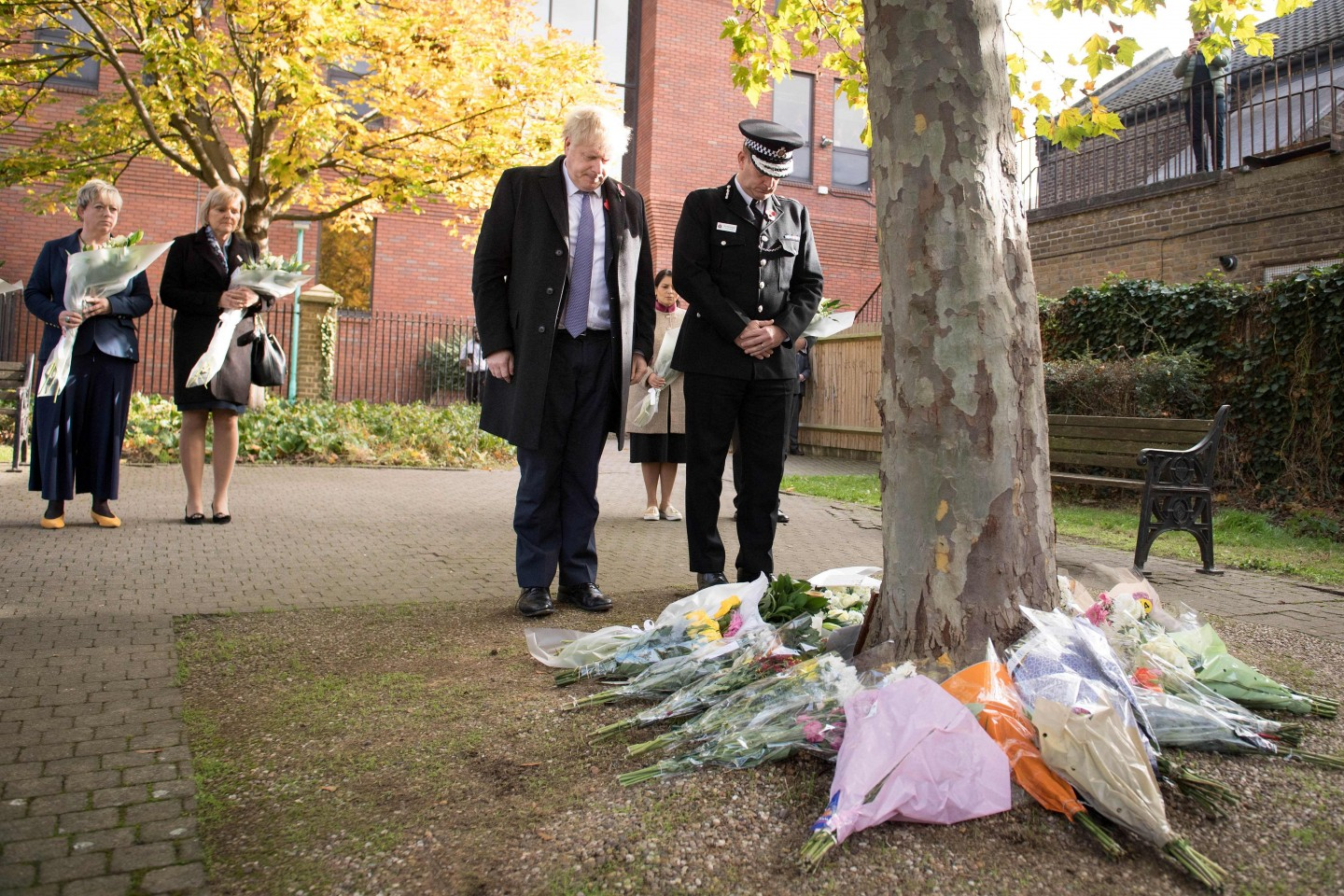 Britain's Prime Minister Boris Johnson stands with Chief Constable of Essex Police, Ben-Julian Harrington (R), after they laid flowers, during a visit to Thurrock Council Offices in Thurrock, east of London on October 28, 2019, following the October 23, 2019, discovery of 39 bodies concealed in a lorry. - British police investigating the deaths of 39 people in a refrigerated truck charged the driver on Saturday with manslaughter and people trafficking, as families in Vietnam expressed fear their loved ones were among the dead. (Photo by Stefan Rousseau / POOL / AFP)