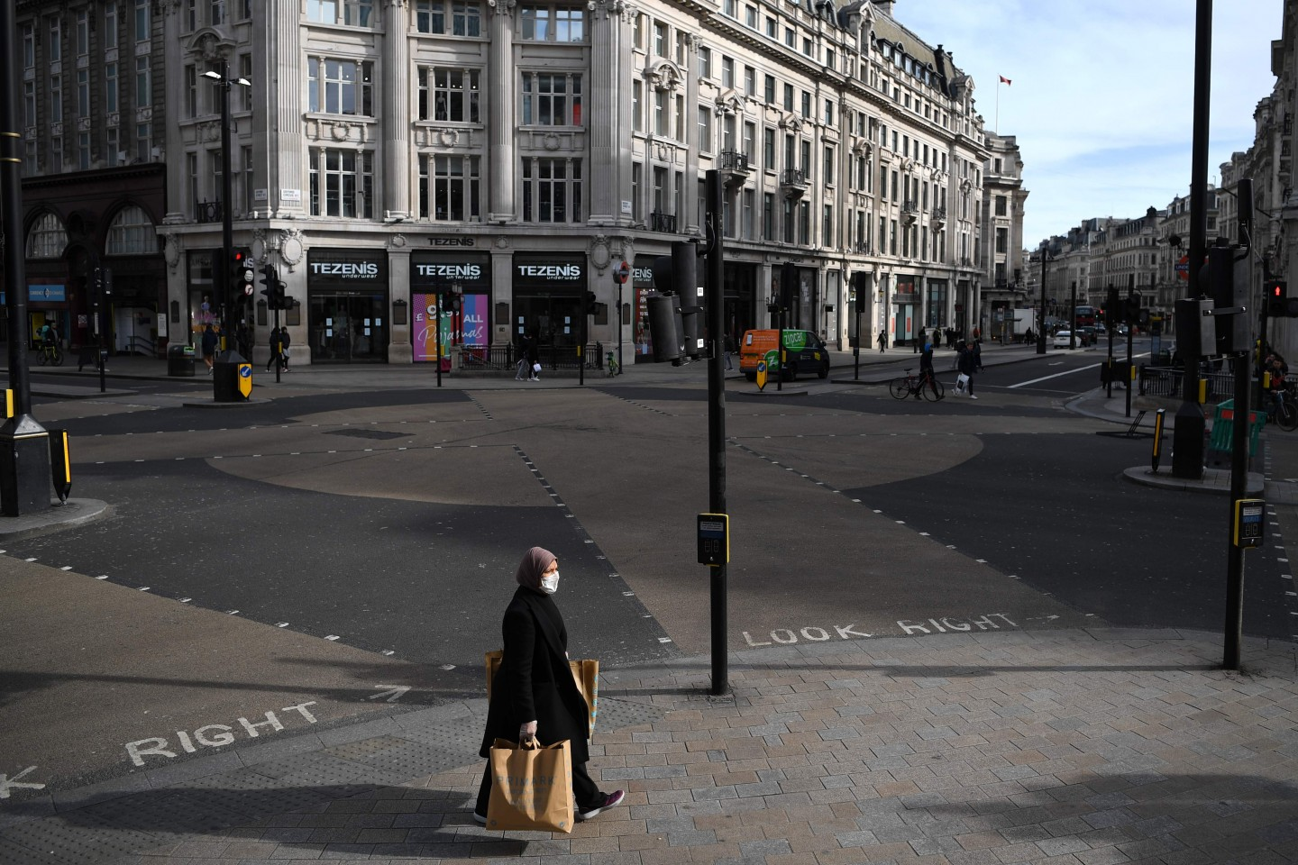 A woman wearing a protective face mask walks through a quiet Oxford Circus in central London on the afternoon of 21 March 2020 (Daniel Leal-Olivas/AFP)