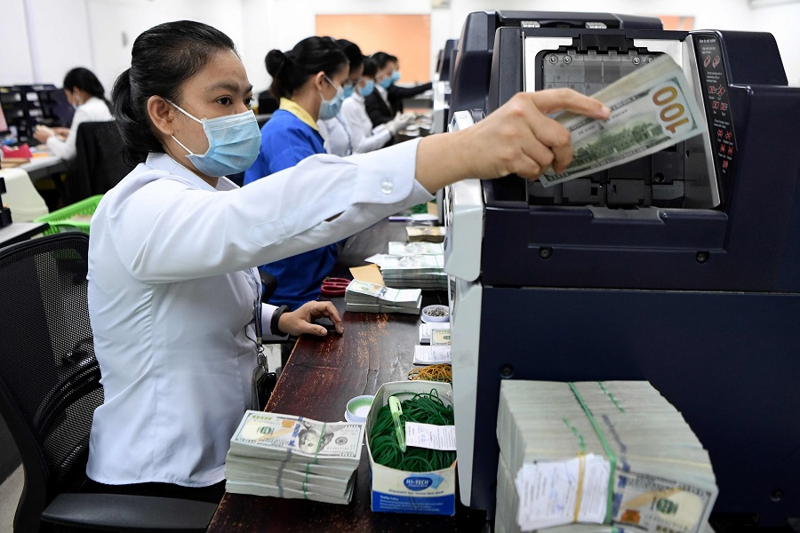 ACLEDA Bank employees count US currency inside the bank in Phnom Penh on 25 May 2020. (Tang Chhin Sothy/AFP)