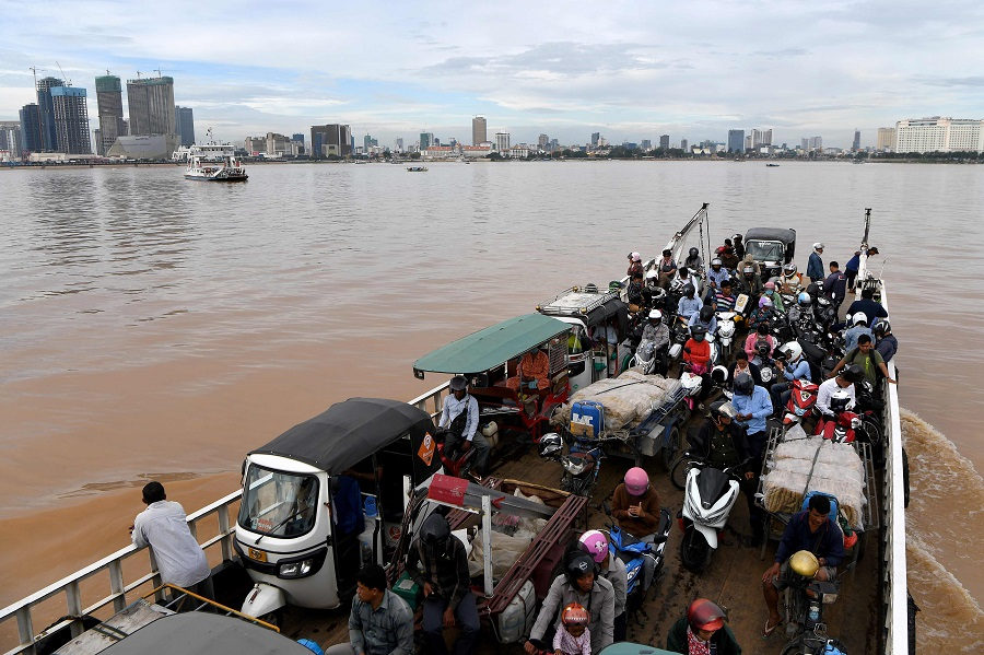 A ferry service transports passengers and vehicles along the Mekong River in Phnom Penh on 25 September 2020. (Tang Chhin Sothy/AFP)