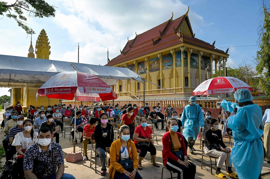 A soldier (right) gives instructions as people wait to receive the second dose of China's Sinopharm Covid-19 coronavirus vaccine at a pagoda in Phnom Penh, Cambodia, on 20 May 2021. (Tang Chhin Sothy/AFP)